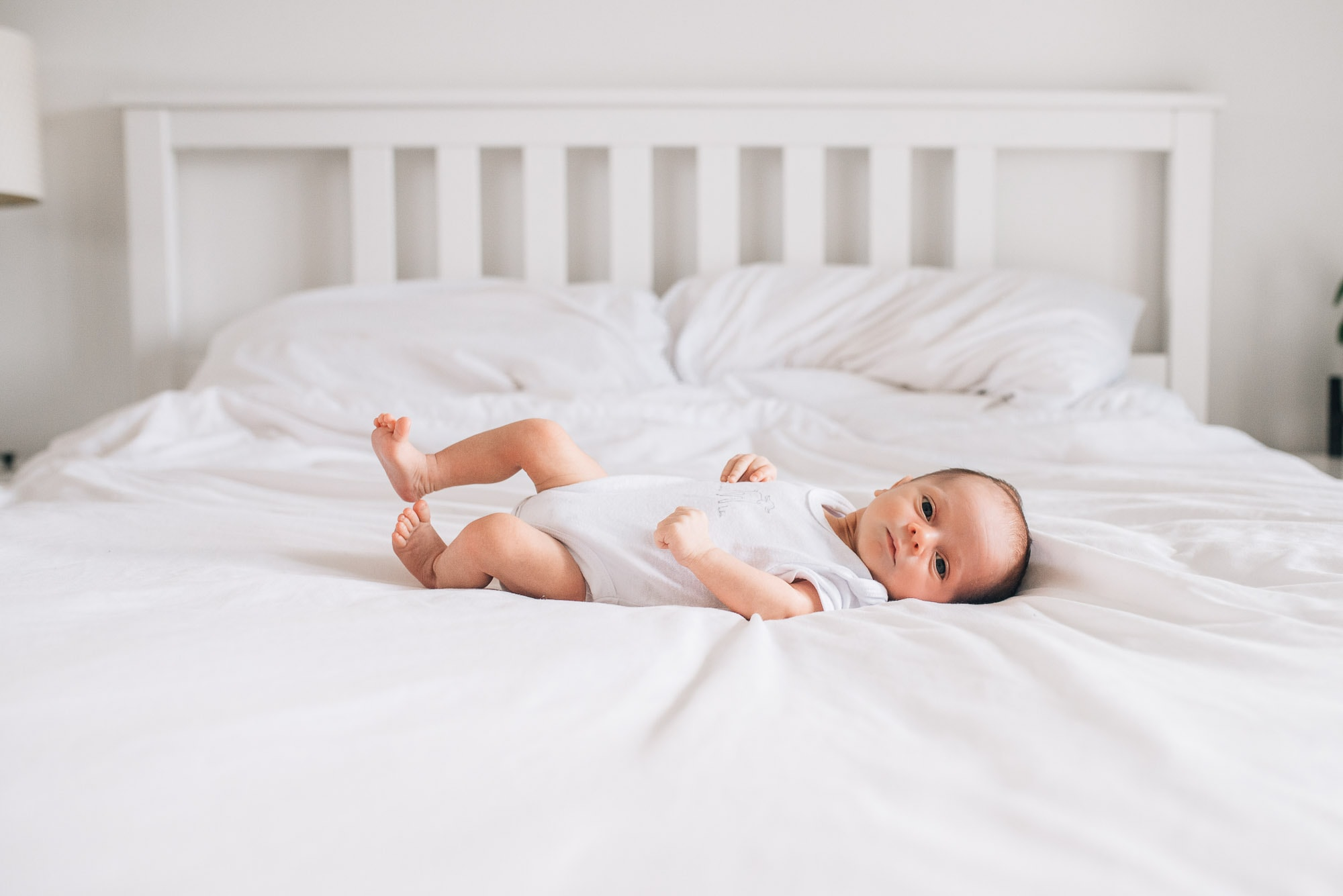 vancouver newborn photographer captures baby lying on bed