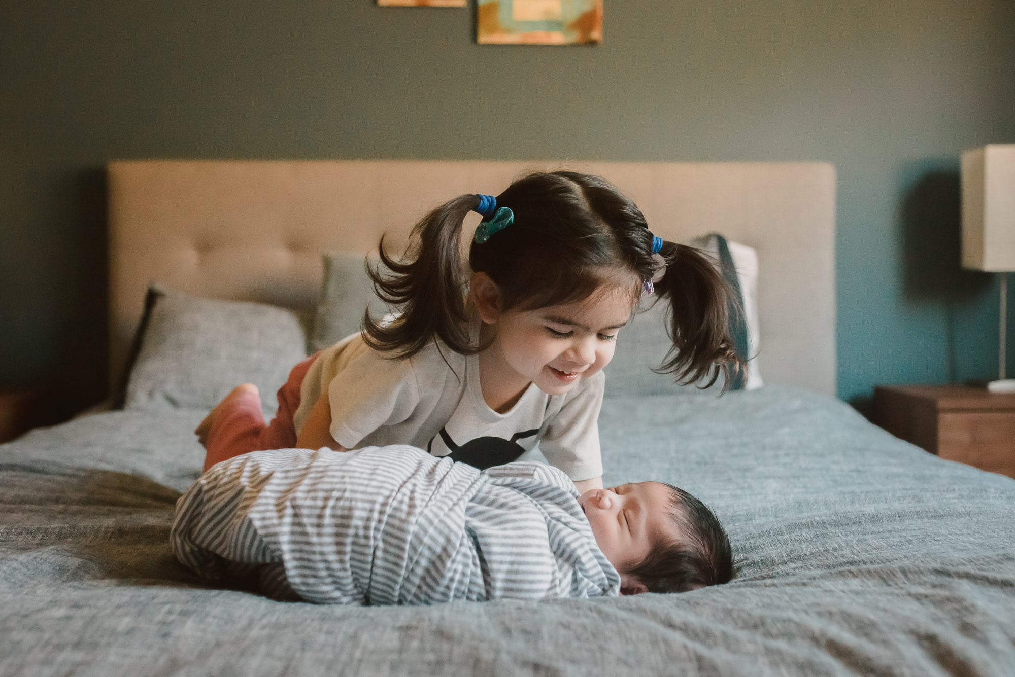 sibling looks at newborn baby on bed during newborn photography session in port coquitlam